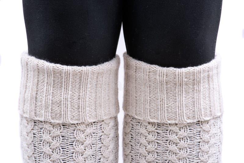 Color de marfil de los calentadores de la pierna del tejido en cable de la mujer que lleva joven aislado en blanco imagenes de archivo