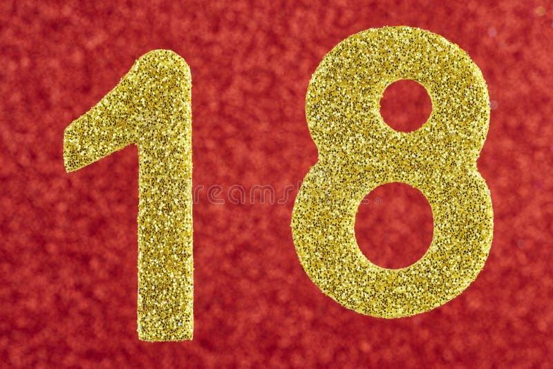 Color de oro del número dieciocho sobre un fondo rojo aniversario foto de archivo