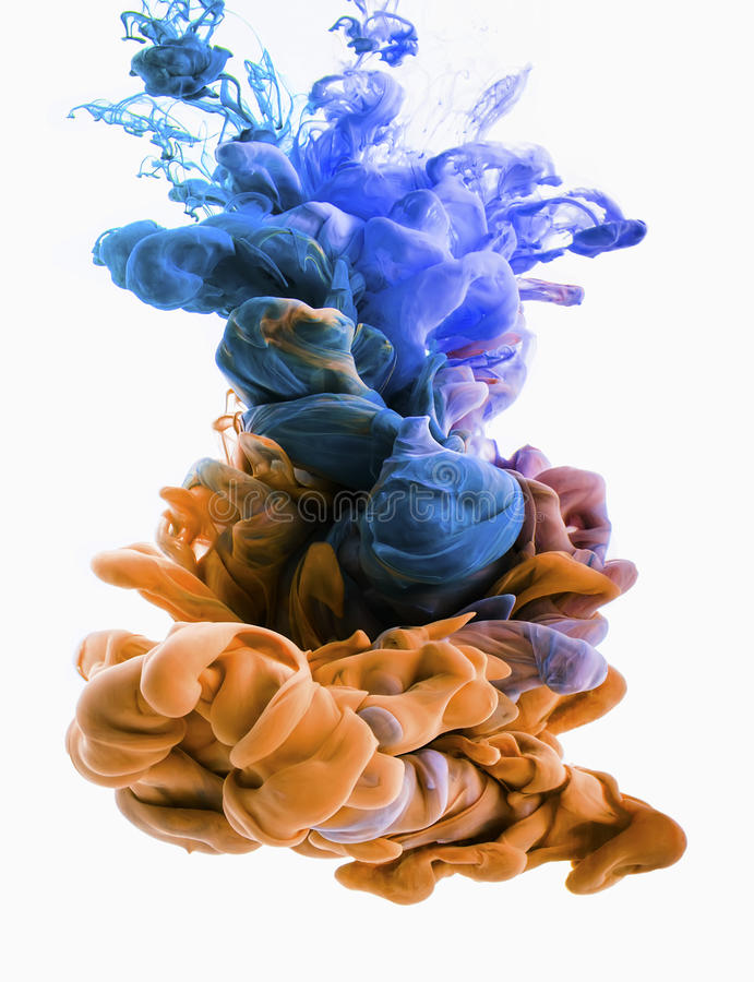 Color drop. gold, blue, turquoise. Colors dropped into liquid, photographed n in motion. Ink swirling in water. Cloud of silky ink in liquid. Colorful ink in stock photography