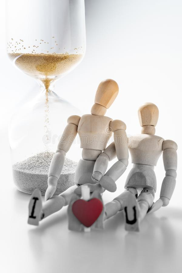 Color fading of time for love. Color fading of time,Miniature wooden mannequin couple holding each other with red heart shape between I and U letters ,sand glass stock photos