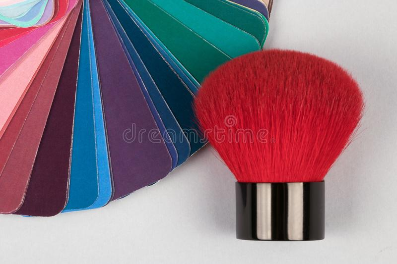 Color fan deck with samples of various paints with red brush for makeup royalty free stock images