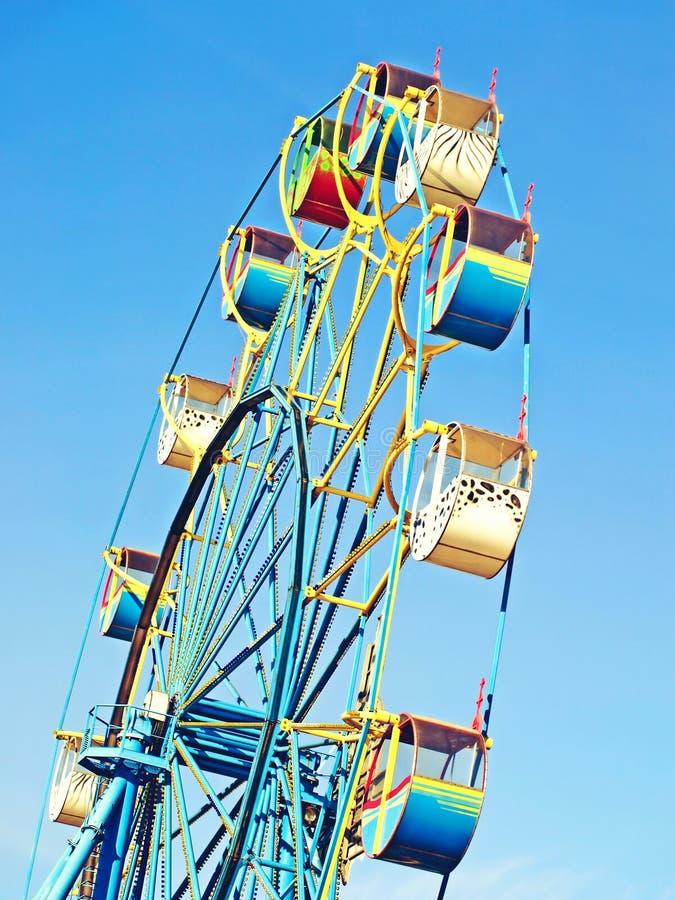 Color Ferris wheel carousel against of the blue sky. Taken closeup stock photos