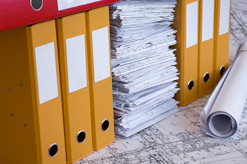 Color file folders and heap of project drawings stock images