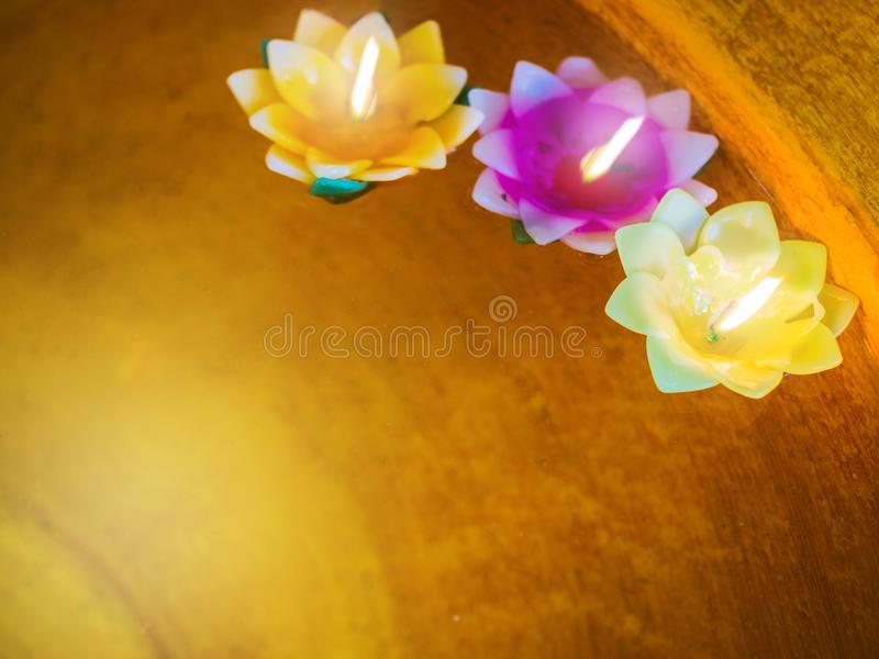 Color filtered: Candle in the flowers colorful holders floating. On water, temple and mindfulness background concept royalty free stock photography
