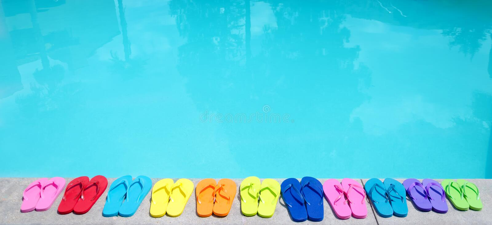 Color flip flops by the pool. Color flip flops by the swimming pool in sunny day royalty free stock image