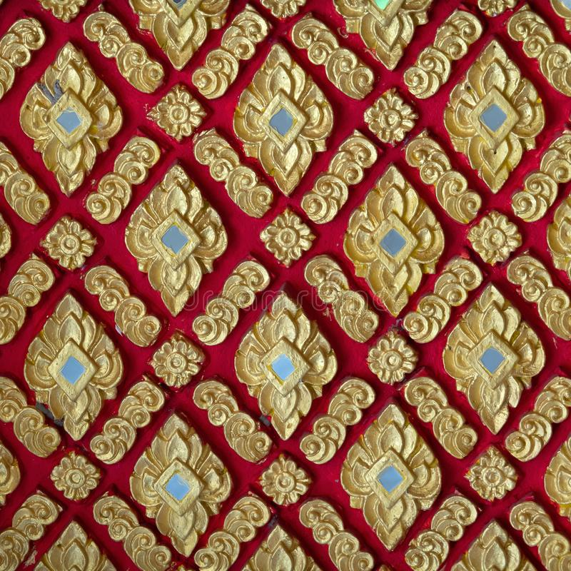 The color golden stucco on red and Thai art wall pattern. Asian, background, antique, design, ancient, architecture, beautiful, abstract, decor, decoration royalty free stock image