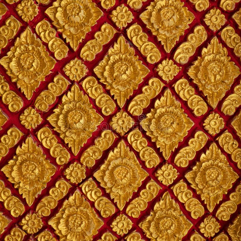 The color golden stucco on red and Thai art wall pattern. Asian, background, antique, design, ancient, architecture, beautiful, abstract, decor, decoration royalty free stock photos