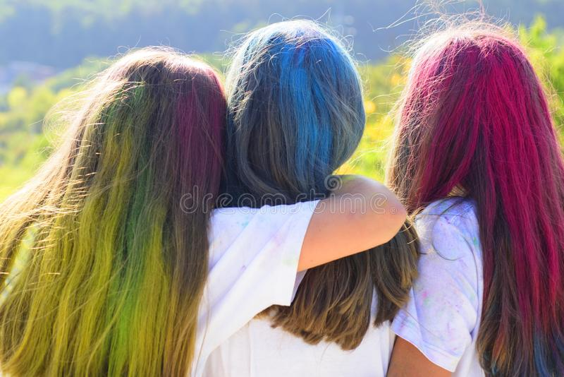 Color hair. Tree best girfriends with colorful hair enjoing in the moment. Colorful holi on painted hair. Happy life in. Teenager time. Back view stock image