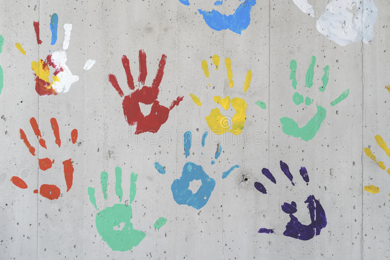 Color hand prints over a concrete wall. stock images