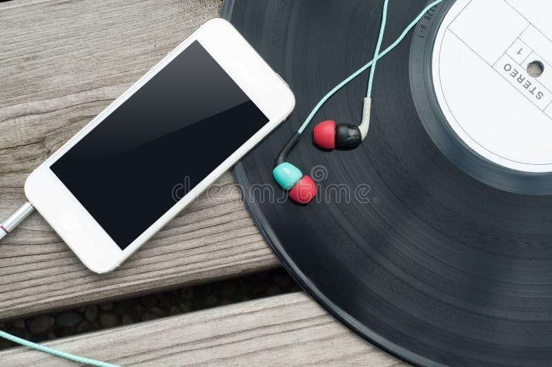 Color Headphones and vinyl. On wooden floor stock images