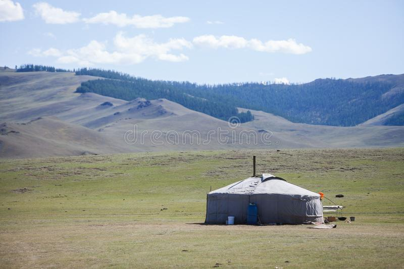 Mongolian yurt on a hill. Color image of a Mongolian yurt on a green field stock images