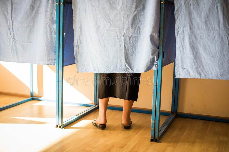 Unidentifiable persons voting in booths at a polling station, during elections. Color image of unidentifiable persons voting in booths at a polling station royalty free stock photo
