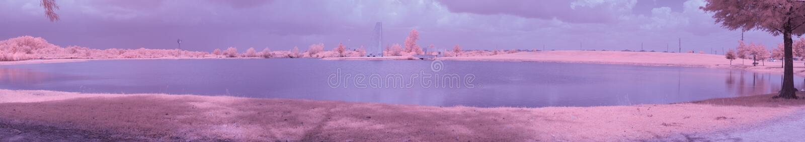 Infrared park lake on a sunny, summer day. A color infrared panoramic of a lake in a park on a summer day royalty free stock images