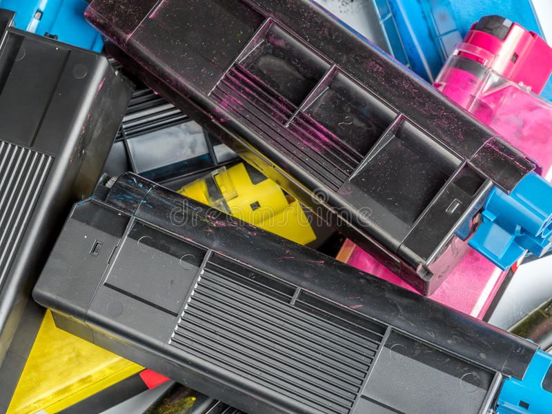 Color laser printer toner cartridges. Pile of used color laser printer toner cartridges royalty free stock photo