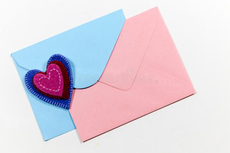 Color letter envelopes and colored hearts. A flat paper container with a flap, used to enclose a letter or document royalty free stock image