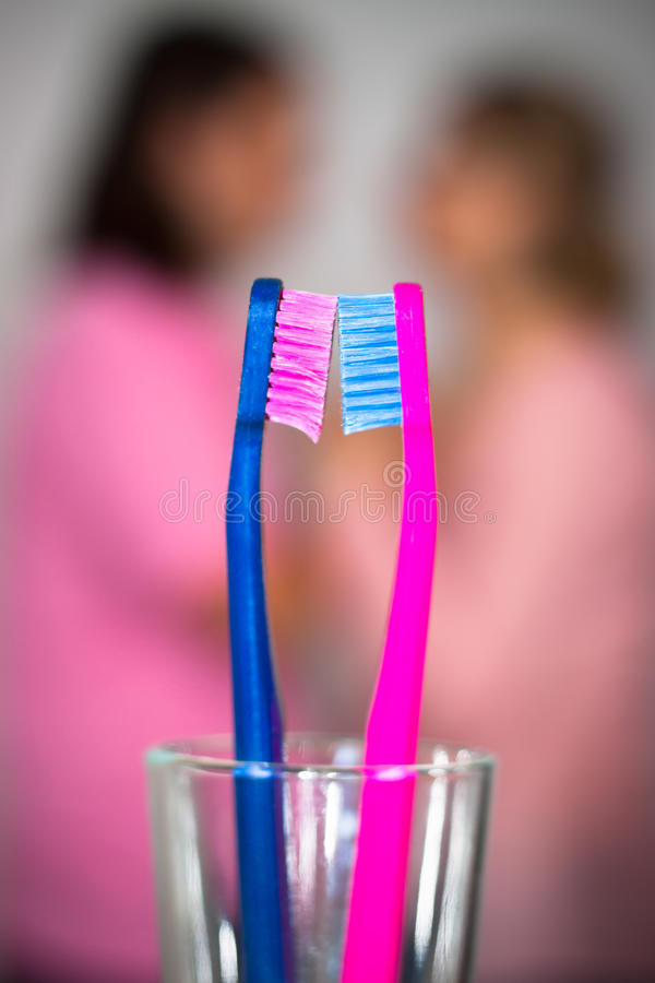 Color of love. Abstract creative photo of pink toothbrushes and blurred couple in love on background, with shallow depth of field