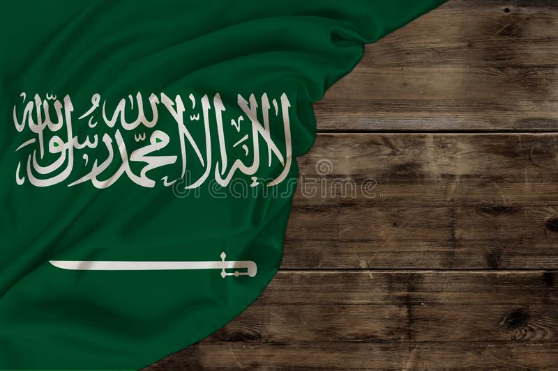 Color national flag of modern state of Saudi Arabia, beautiful silk, old wood background, concept of tourism, economy, politics,. Emigration, independence day stock photos