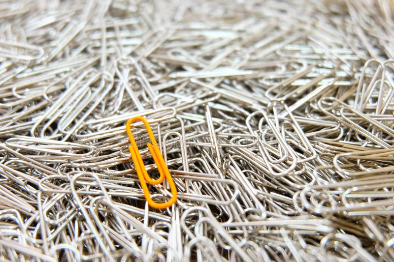 Orange paper clip on multiple paper clips background. Color Orange paper clip on multiple paper clips background stock photo