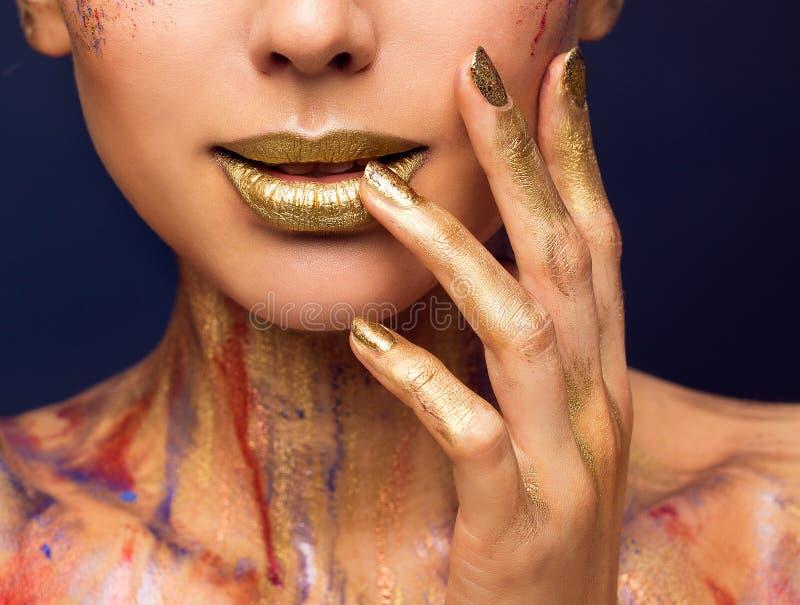 Color oro de los labios, maquillaje de la belleza de la moda, clavos pintados mujer de la cara foto de archivo libre de regalías