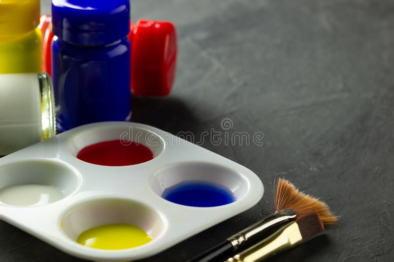Color palette and artist paint brush with poster color bottle on the floor. Color palette and artist paint brush with poster color bottle on black cement floor stock photo