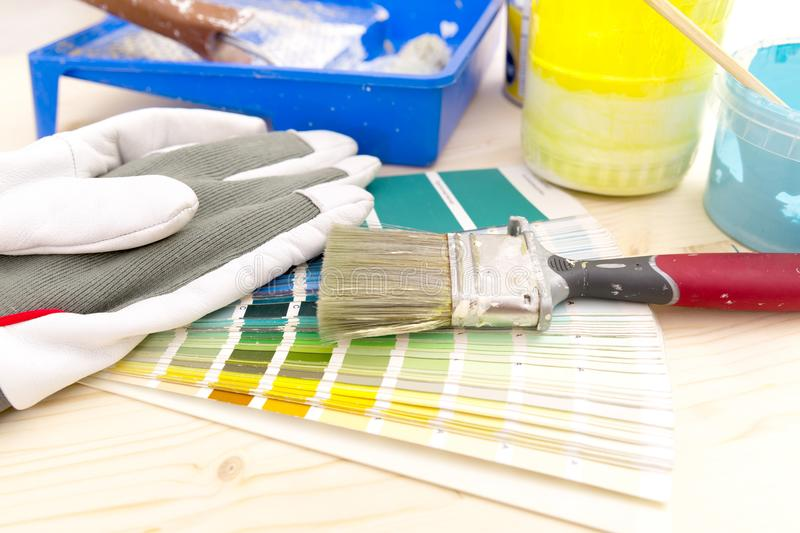 Color palette guide and painting supplies, paint brushes and col. Or cans on wooden background royalty free stock photo