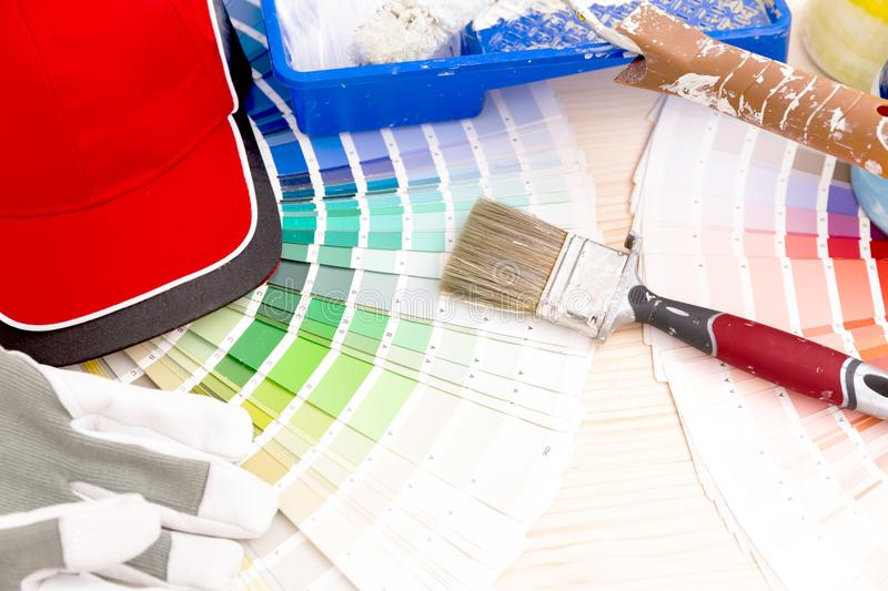 Color palette guide and painting supplies, paint brushes and col. Or cans on wooden background stock image