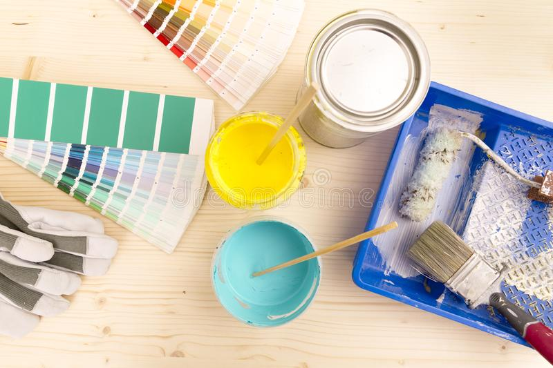 Color palette guide and painting supplies, paint brushes and col. Or cans on wooden background stock photos