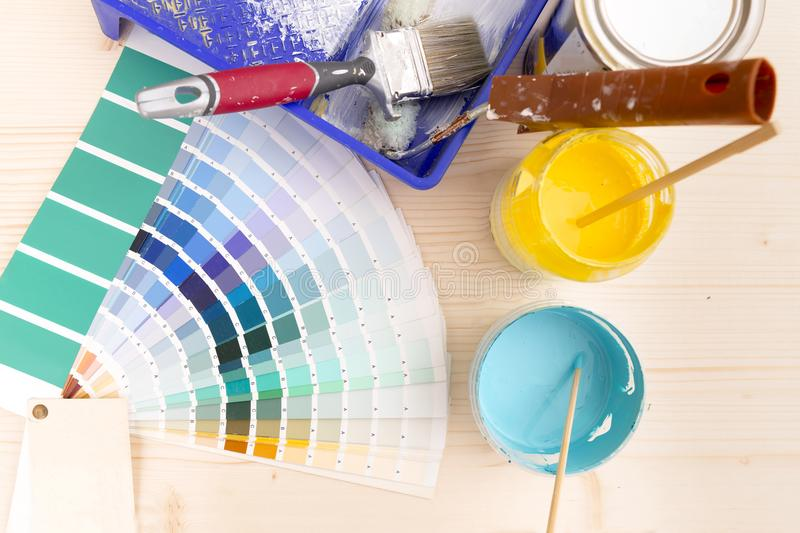 Color palette guide and painting supplies, paint brushes and col. Or cans on wooden background stock photography