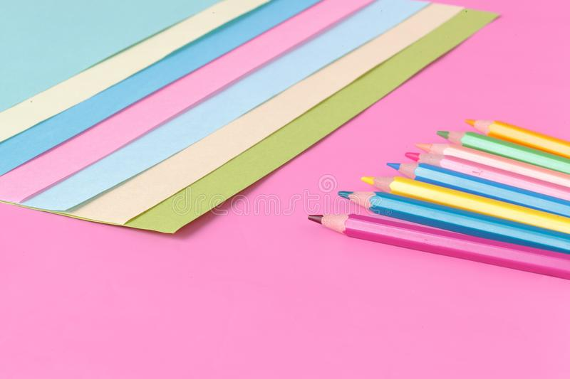 Color paper and pen on pink background, creative concept stock photos