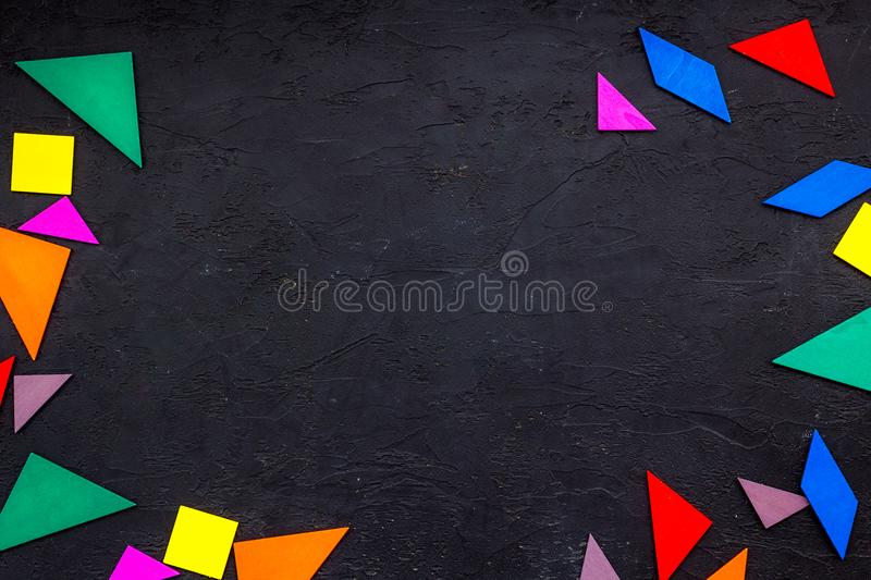 Color paper pieces for business puzzle black table background top view space for text stock photography