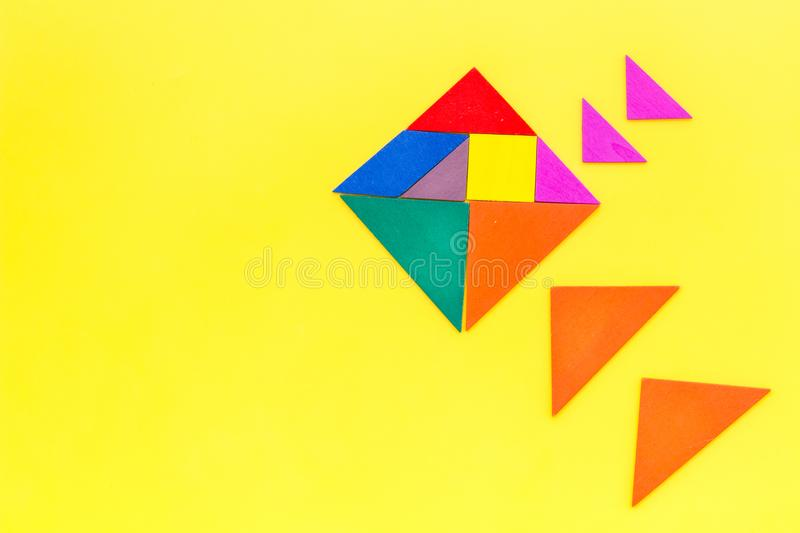 Color paper pieces for business puzzle yellow table background top view space for text stock photography