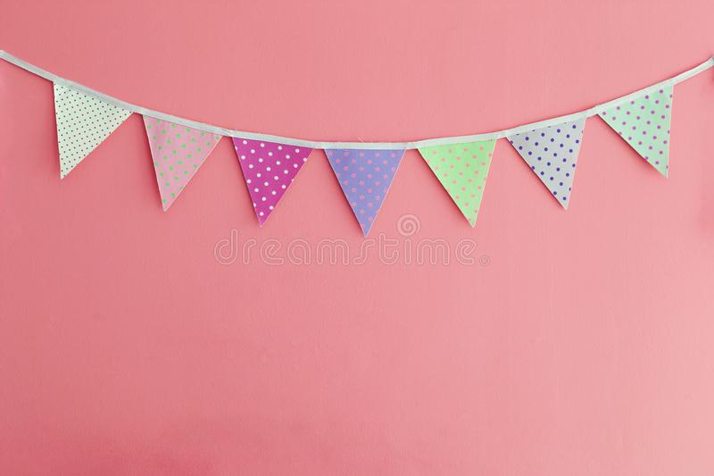 Color party bunting banner cotton triangle flag over red wall. Texture background stock photography