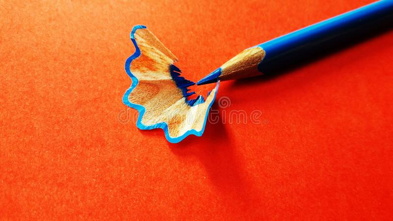 color pencil with its shave isolated on orange background stock image