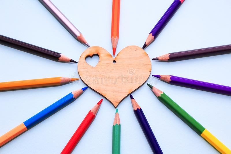 Color pencils in arrange in color wheel colors around wooden heart on blue background. Vie top. A free place for text stock image