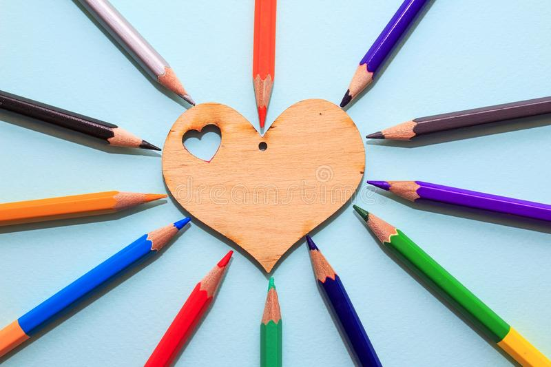 Color pencils in arrange in color wheel colors around wooden heart on blue background. Vie top. A free place for text royalty free stock photos