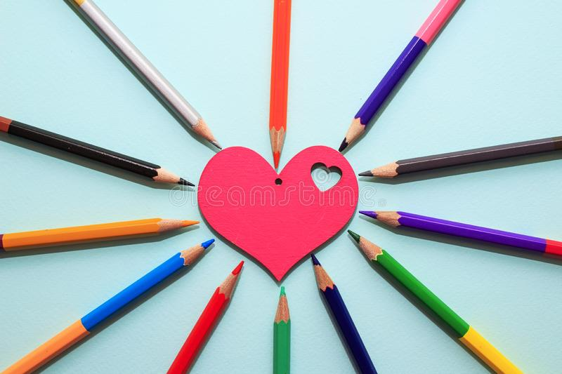 Color pencils in arrange in color wheel colors around wooden red heart on blue background. Vie top. A free place for text stock photo