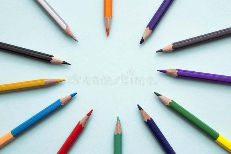 Color pencils in arrange in color wheel colors on blue background. Vie top. A free place for text royalty free stock image