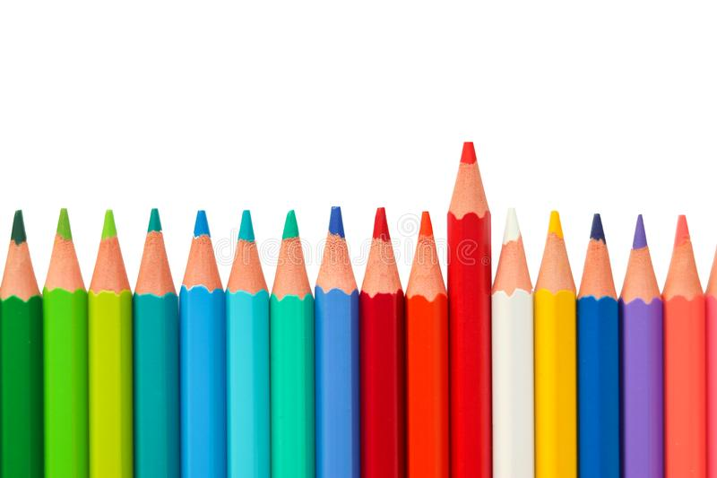 Color pencils arranged horizontally in a line on white background with one standing out from the rest, with space for text. royalty free stock images