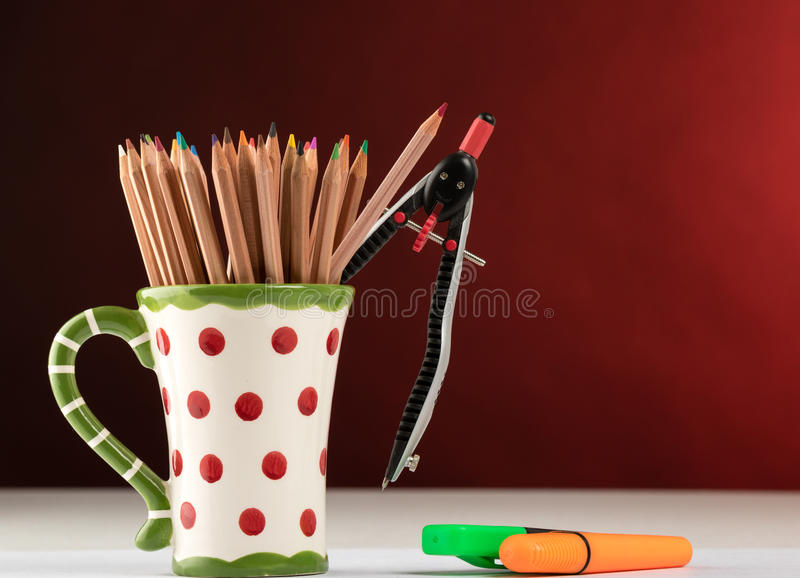 Color pencils in a mug. On a table with red background stock photography