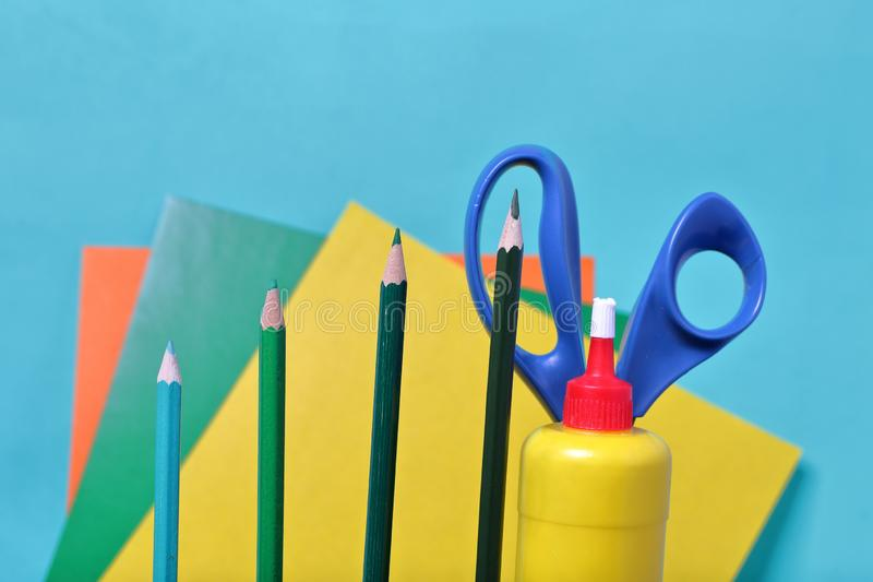 Color pencils. Scissors, glue and colored paper for application. They are located vertically. Color pencils in green shades. Scissors, glue and colored paper for stock images