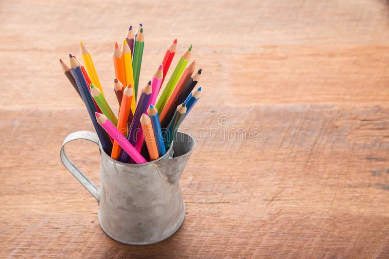 Color pencils in tin can, wood table background. education concept royalty free stock photo
