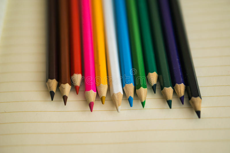 Color pencils on white notebook background.Close up. Concept shcool stock photos