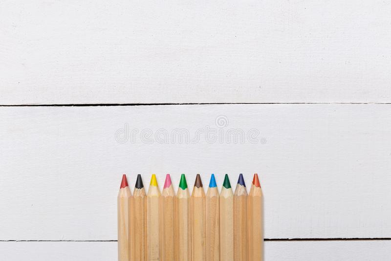 Color pencils on white wooden background royalty free stock images