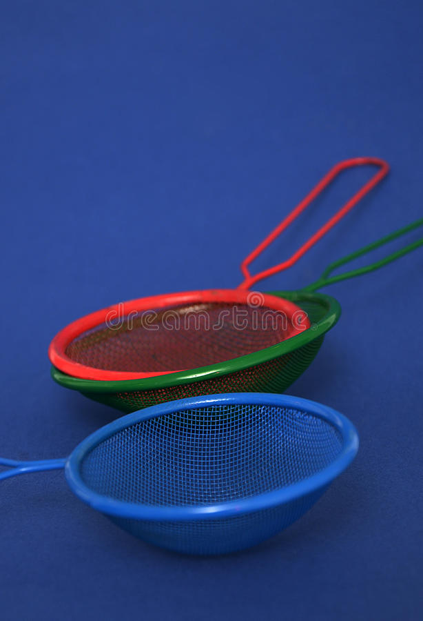 Color and photography concept. Picture of a red , green and blue tea strainers royalty free stock photos