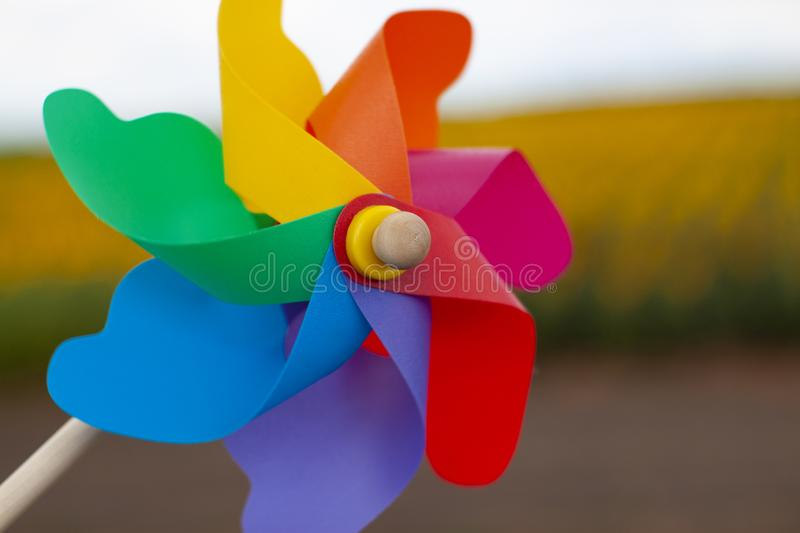 Color pinwheel toy against summer sky. Close-up colorful pinwheel in a garden. color pinwheel toy in sunny summer day stock image