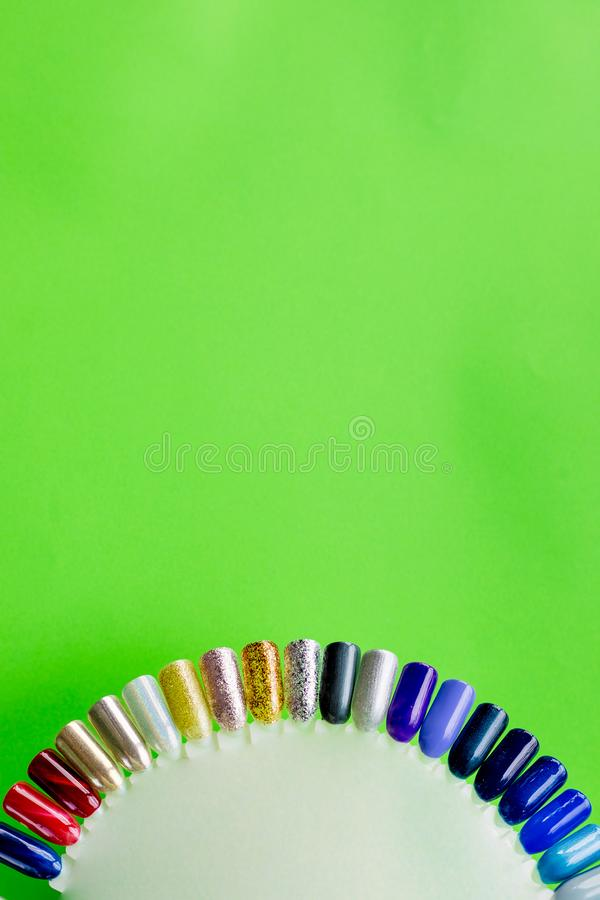 The color of Polish for manicure. design for nails. testers nail Polish on green background.Fashion manicure. Shiny gel stock photography