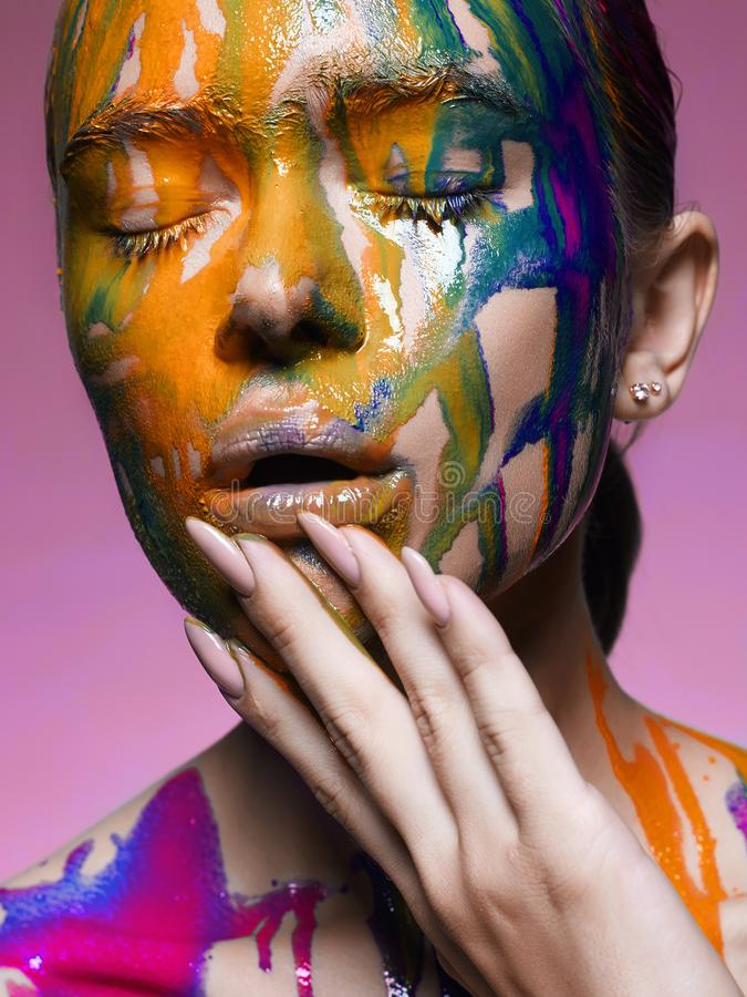 Color portrait of Girl in Paint. Liquid paint flowing over a beautiful face and Body. Colors stock images