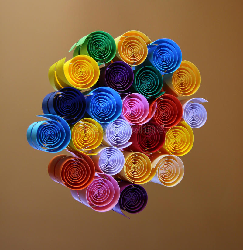 Color of rainbow. Coloured ribbons spinning around. Set of paper strings from an art shop, shaped into a circles in the colours of a rainbow stock image