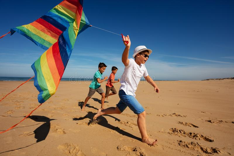 Color rainbow stripped kite hold by boys on beach stock image