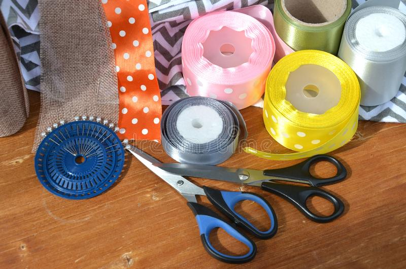 Color ribbons, scissors and pins set on wooden plank stock photo